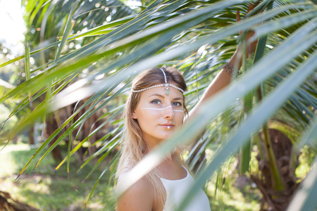 Phangan, Thailand. A beautiful young woman stands in a palm grove in the rays of the morning sun.