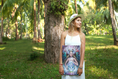 Phangan, Thailand. A woman artist stands under palm trees with a picture in her hands. Phangan, Thailand.
