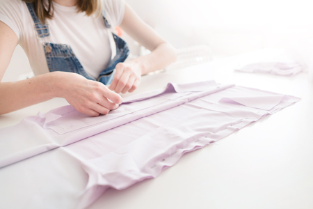 tailor girl cuts cloth with scissors. sewing business Standard-Bild