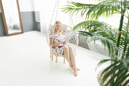 lifestyle concept. blond girl is sitting in a rocking chair. talking on the phone. Standard-Bild