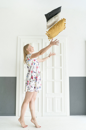 young woman tosses pillows at home. Ease and coziness.  Lifestyle concept.