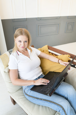 girl is sitting in the chair with a laptop. Work at home. Remote business. Freelance.