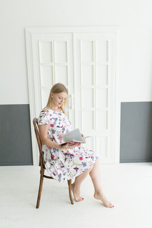Full length portrait of a happy joyful blonde woman sitting on the chair with opened magazine. Lifestyle concept. 免版税图像