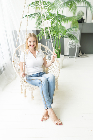 Young woman chilling at home in comfortable hanging chair. Girl relaxing  swing in loft living room. Lifestyle concept.