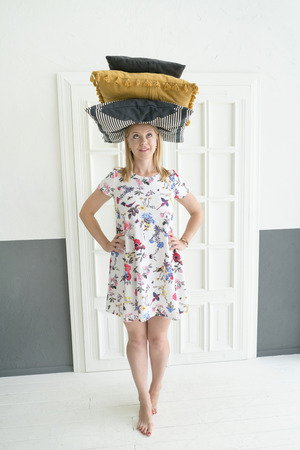 A young woman is standing with pillows at home. Stability and coziness.  Lifestyle concept.