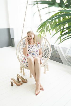 lifestyle concept. blond girl is sitting in a rocking chair. talking on the phone. 免版税图像