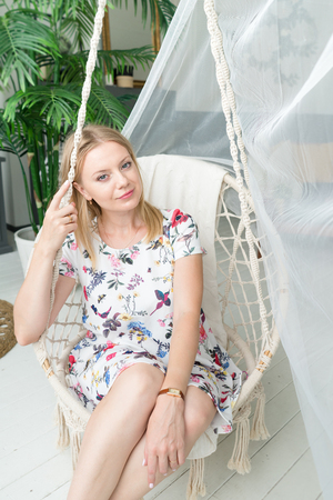 lifestyle concept. blond girl is sitting in a rocking chair Standard-Bild