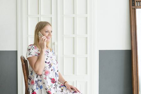 Head shot of positive carefree girl speaking on smart phone with lover sharing gossip secrets with friend having beaming smile using cell phone sitting on chair indoor