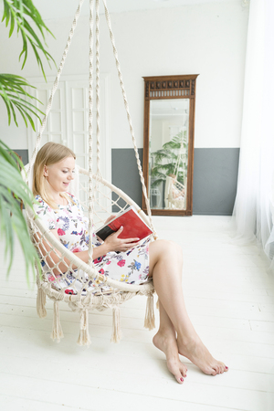 lifestyle concept. blond girl is sitting in a rocking chair. read magazine.