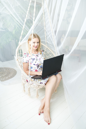 Young woman feeling happy relaxed sitting at desk with laptop, smiling freelancer enjoys distance online job stretching at home workplace, motivated girl satisfied with good news or having work break