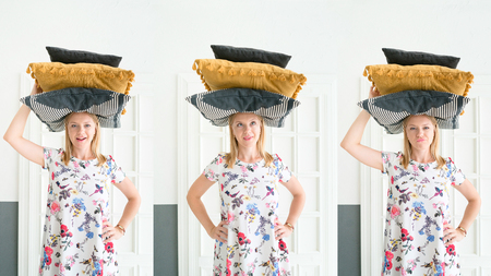 Young woman holding pillows on her head at home. Stability and coziness.  Lifestyle concept.