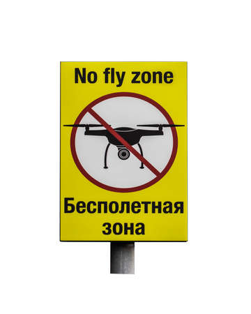 Prohibition sign No fly zone in Russian and English. Yellow prohibition sign with crossed out silhouette of a flying aircraft drone isolated on a white background. You can not fly in this area