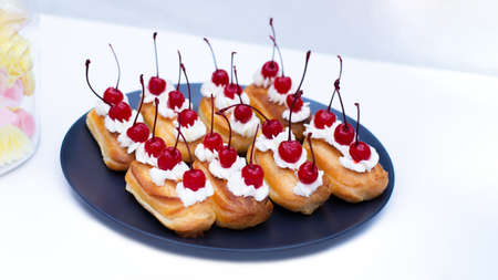 French Eclair cakes profiteroles on a cinnamon plate. Sweet pastries with cream and cocktail cherries, dessert on a white background