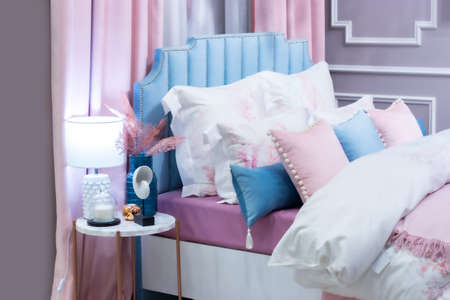 Defocus background of a beautiful bedroom in pastel pink blue. A large bed, a bunch of pillows, a bedside table with a lamp vase and decorations. Home decor, bedroom for a girl