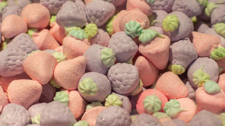 Airy marshmallows in the shape of a pink purple strawberry, close-up background wallpaper. Sweet candy marmalade in a supermarket. A large pile of fruit berry sweets with sugar Banco de Imagens