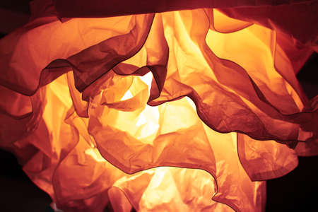 Abstract defocus background orange backdrop, crumpled paper lit by a lamp. Color of the Year 2020 Lava backdrop background wallpaper, photo tinted in trendy Lava orange color