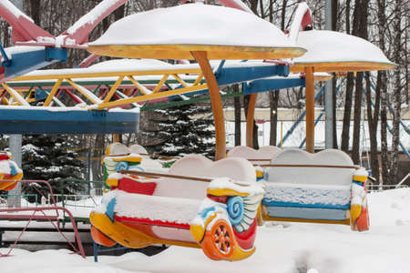 Carousel in the snow, a bright multi-colored fun ride empty littered with snow, winter is not the season for a carousel 免版税图像