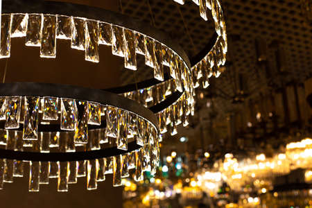 Crystal glass chandelier with thin transparent plates, abstract illumination, warm light backdrop background. Large chandelier with crystal rectangular plates, glass refracts light