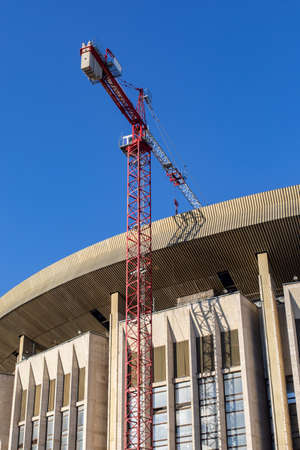 Reconstruction of a broken sports complex. The roof and facade of a large building, construction crane, vertical. Renovation, restoration of broken buildings in the city, construction of a new stadium