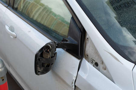 Torn car mirror hanging on wires, consequences of a car accident. Collision of transport, breakdown of car sedan, details close-up