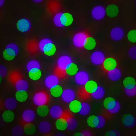 Abstract defocus background, colored green red violet purple dot circle. Illumination blurry lights, pixelated dotted abstract picture of rainbow light spots, electric LED lighting