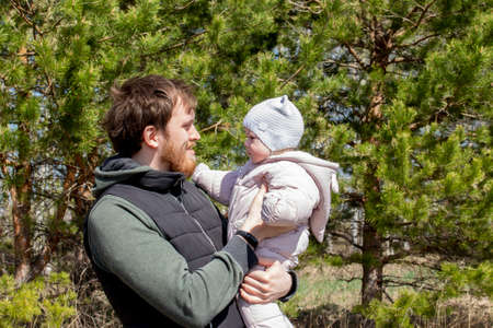 A father with a baby in his arms is walking in the park. A young man with a beard holding a child girl, 9 months old. Dad and daughter in spring clothes on a background of green trees Stockfoto
