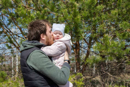 A young father kisses a newborn daughter, a walk in the park, a dad with a baby girl tenderness love care, a loving parent family portrait Stockfoto