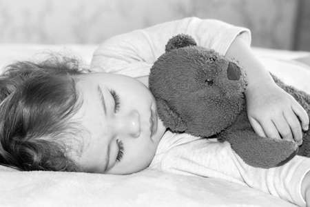 Little baby sleeping hugging a teddy bear, closeup portrait black and white. The child 1 year. Caucasian girl boy dreaming in the afternoon Banco de Imagens