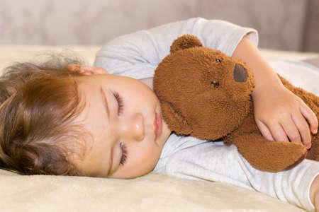 Little baby sleeping hugging a teddy bear, closeup portrait. Child girl Caucasian boy sleeping sweetly in bedroom