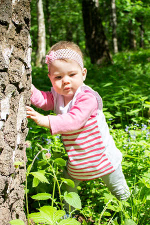 baby girl walks in the park, learns to walk, holding onto a tree trunk. A child of 10 months studying nature. A girl in a pink striped dress with a bow. Portrait of a baby girl european caucasian