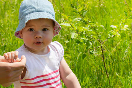 Baby girl portrait close-up, walk in nature, green meadow. Curious child, girls in summer hat
