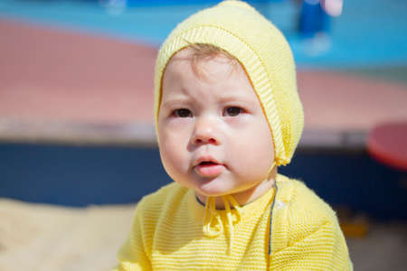 Face baby girl boy 1 year old portrait close-up. The child in a yellow knit hat outdoors