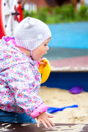 The child screams while sitting in the sandbox. The baby in the cap opened his mouth. Baby girl walks in the yard on the playground, vertical