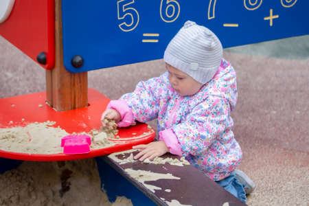 Baby girl playing with sand. A girl in a pink jacket and hat for a walk plays with sand in a sandbox, picks up sand, studies the world around. A small child walking in the courtyard