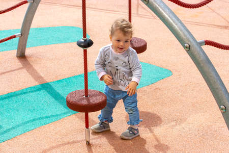 Little child girl boy on the playground. 1 year european caucasian, kid in jeans curly hair