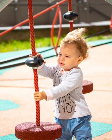 Toddler 1 year old girl boy Caucasian, playing on the playground, baby with wavy blonde hair in the wind, vertical sunny bright 版權商用圖片