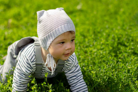 Baby girl boy crawling on the green lawn. Portrait of a child close-up. The baby learns to crawl. Gray clothes, hat, waterproof overalls and striped jacket