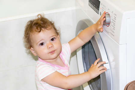 Little Caucasian baby girl 1 year turns the button of the washing machine, home life childhood household appliance