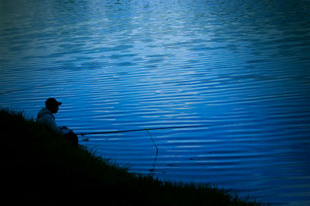 Night fishing, dark silhouette of a fisherman with a fishing rod sits on the shore the background of dark blue water, a man catches fish in the moonlight