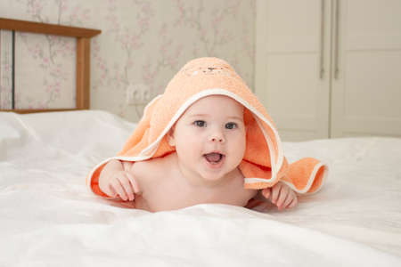 Baby Caucasian girl boy 5 months crawls out from under the towel, cheerful laughing open mouth, soft focus