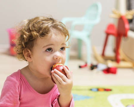 Little Caucasian baby girl in pink bites an apple. A child with curly short hair in the home interior, portrait of a girl of one and a half years old