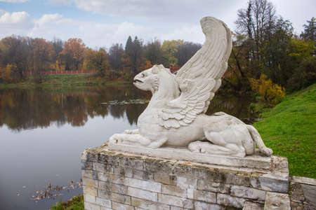 Stone concrete lion with wings statue, gargoyle on the stone pedestal, decoration of the manor park, the shore of the pond of the lake autumn landscape. Sculptural composition on the lake Imagens