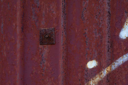 Texture of rusty metal surface with a patch. An old rusty sheet of iron with an old bolt corroded by rust and weather. Textured effect background backdrop for design