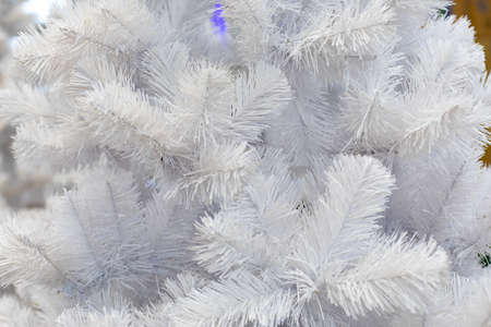 White artificial Christmas tree branch, silvery long needles of eco spruce pine. Festive Christmas backdrop background for design, New Year decoration.