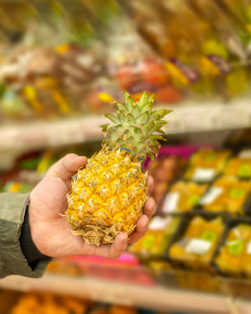 Pineapple in a man's hand in a supermarket. Buying ripe tropical fruits in the store. Golden pineapple in a supermarket showcase, shopper making a choice