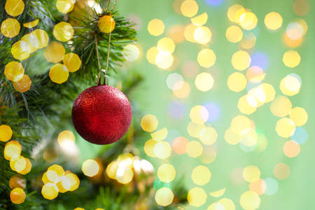 Christmas decoration red toy ball on a branch of a christmas tree, christmas tree toy, sparkling shiny background copy space design