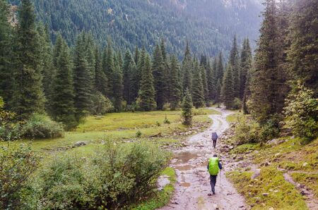 Small figures of people on a trail surrounded by a majestic mountain scenery Stok Fotoğraf