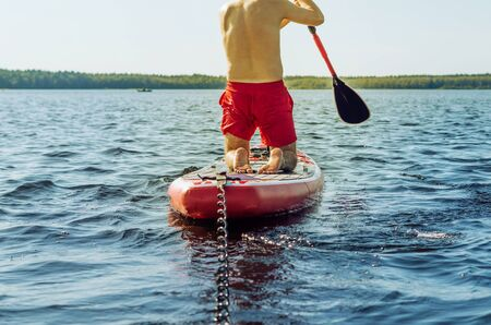 Anonymous man standing on his knee and paddling on a stand up paddle (SUP) board on a lake in the wild