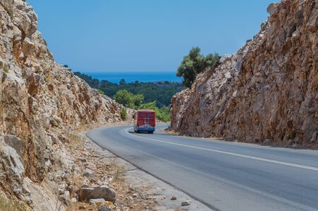 Bus driving along a rocky road in Rhodes, Greece