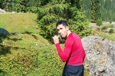 man brushing teeth in the mountains near the river